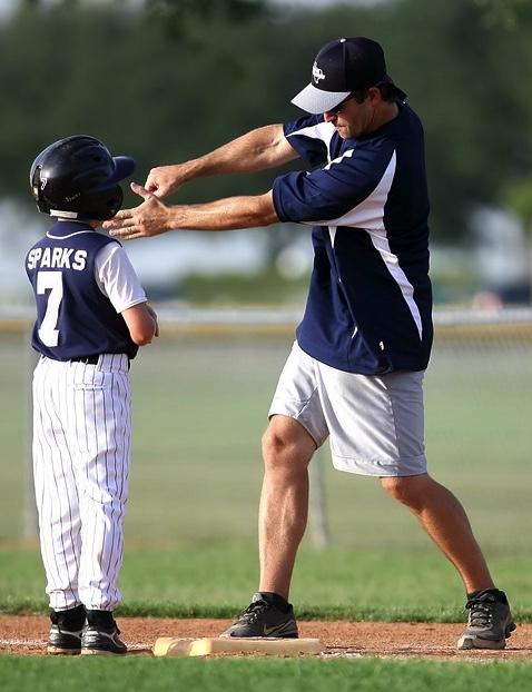 野球のコーチが子供に打ち方を伝えている